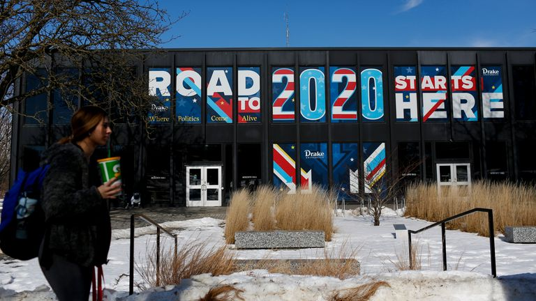 """A woman walks past a sign displayed on a building a Drake University that reads """"Road To 2020 Starts Here"""" on February 2, 2020 in Des Moines, Iowa"""