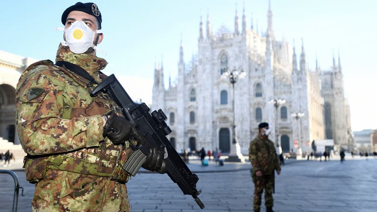 Military officers wearing face masks stand outside Duomo cathedral, closed by authorities, in Milan