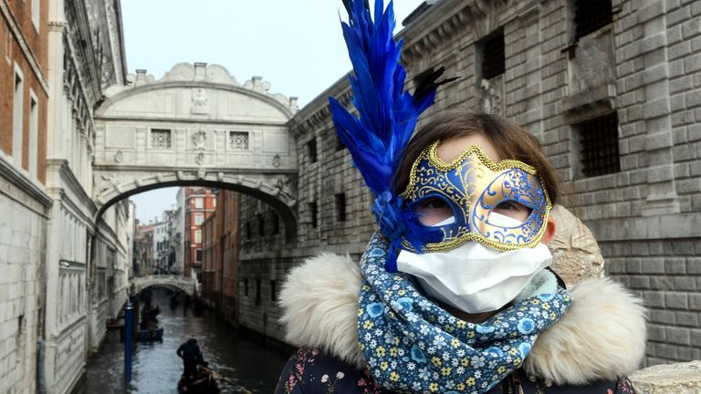 A young tourist wearing a protective and a Carnival mask in Venice