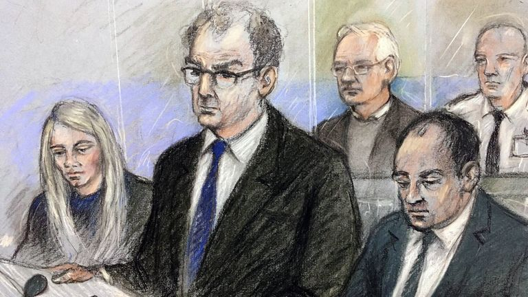 Julian Assange (back) listened in the dock as James Lewis (front, centre) opened the hearing with the US position