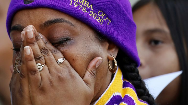 LOS ANGELES, CALIFORNIA - FEBRUARY 24: A fan becomes emotional while watching a live broadcast of the 'Celebration of Life for Kobe and Gianna Bryant' memorial service on a fan's iPad outside the Staples Center on February 24, 2020 in Los Angeles, California. Some fans were disappointed that the Staples Center didn't broadcast the event on television screens outside for those who didn't have tickets.