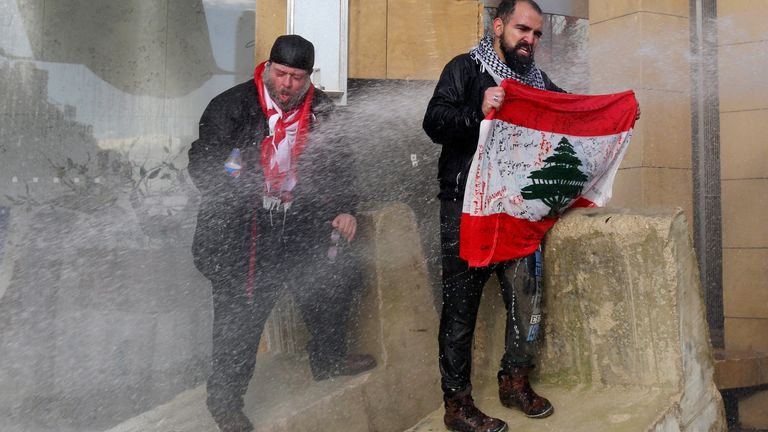 Demonstrators in Beirut are sprayed with a water cannon while trying to prevent MPs reaching the parliament