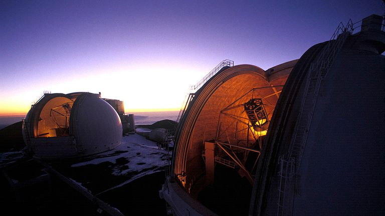 "UNDATED PHOTO:  Atop the highest peak in the Pacific, Mauna Kea, the dome shutters of Keck I and II open as night begins to fall at 13,800 feet above sea level 1999 on Hawaii, The Big Island.  Both Keck I and II, partners on Mauna Kea, are among the most advanced telescopes in the world.  Each is ten meters wide with a mirror comprised of 36 hexagonal segments that can be individually manipulated by computer.   The questions man has tried to answer by looking to the heavens with such powerful telescopic tools are at the very center of his search for meaning in his individual life as well as meaning in general.  How and why are we here?  Are there others like us out there?  How did what we understand as the universe external to us come to exist and will it continue to exist?  Indeed, did it ever begin to exist or is it eternal?  It is hoped that the study of the universe, or ""cosmology,"" including how stars, galaxies, black holes, etc. are formed and how they evolve, with more and more complex telescopes driven by more and more complex computers, will answer these questions.  But it seems that as each more powerful observatory comes online, yet more probing questions arise.  Will we ever uncover the secret of the true nature of the universe and thus the reason for existence in general and our existence in particular?  Sometimes it seems unlikely, but not for man's lack of trying and his indefatigable intellectual tenacity.  (Photo by Joe McNally/Getty Images)"