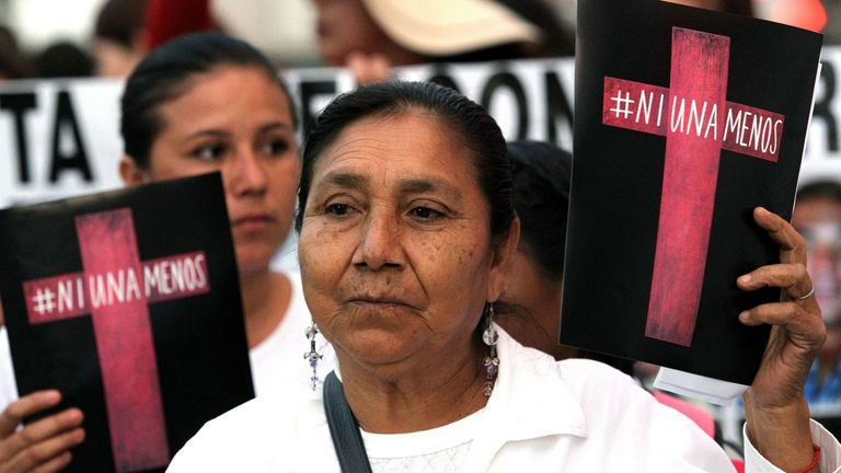 A woman in Guadalajara with a sign reading: 'Not one less'