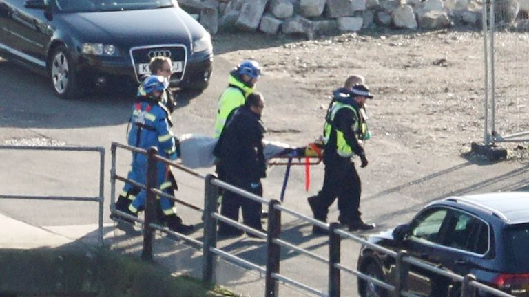 A suspected migrant is brought ashore on a stretcher in Dover