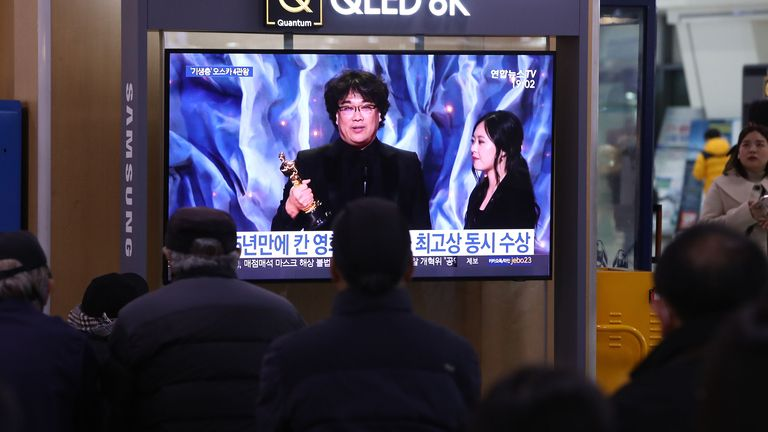 "People watch a TV screen showing images of South Korean director Bong Joon Ho at the Seoul Railway Station on February 10, 2020 in Seoul, South Korea. Bong Joon-ho's ""Parasite"" has bagged four Oscar titles, becoming the first non-English language film to win best picture"
