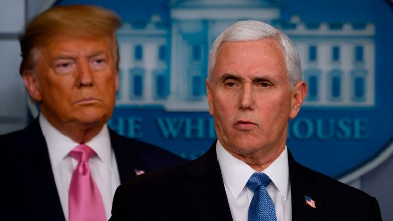 US President Donald Trump (L) looks on as US Vice President Mike Pencespeaks during a news conference on the COVID-19 outbreak at the White House on February 26, 2020. - US President Donald Trump on Wednesday defended his administration's response to the novel coronavirus, lashing the media for spreading panic as he conducts an evening news conference on the epidemic