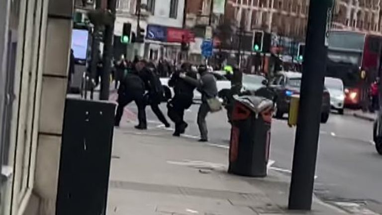 Armed police approach the figure on the ground. Image 4.