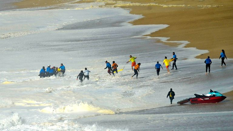 Surfers and technical team help the Portuguese surfer Alex Botelho. Pic: Carlos Barroso/EPA-EFE/Shutterstock