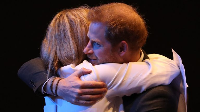 Prince Harry is hugged during an event in Edinburgh
