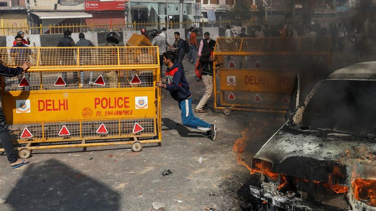 Supporters of a new citizenship law tore down police barricades during clashes with opponents in New Delhi