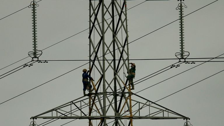 Workers paint an electricity pylon