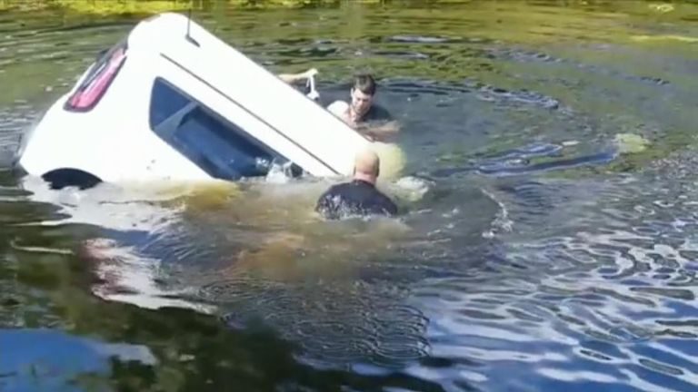 Bystanders rushed to help a woman who had driven her vehicle into a canal while having an epileptic seizure