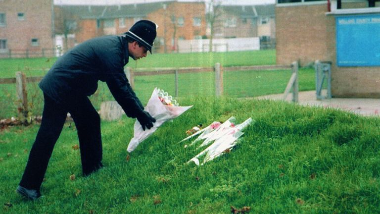 A policeman leaves flowers at Welland County Primary School in Peterborough, the school of murdered six-year-old Rikki Neave, whose naked body was found dumped in undergrowth 500 yards from his home.