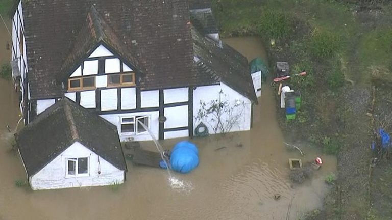 Water is pumped from house surrounded by flood near River Severn