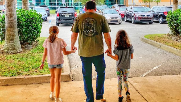 Ryan Newman walking out of hospital with his daughters.