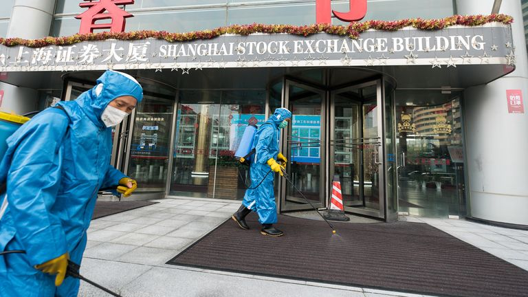 Medical workers spray antiseptic outside of the main gate of Shanghai Stock Exchange