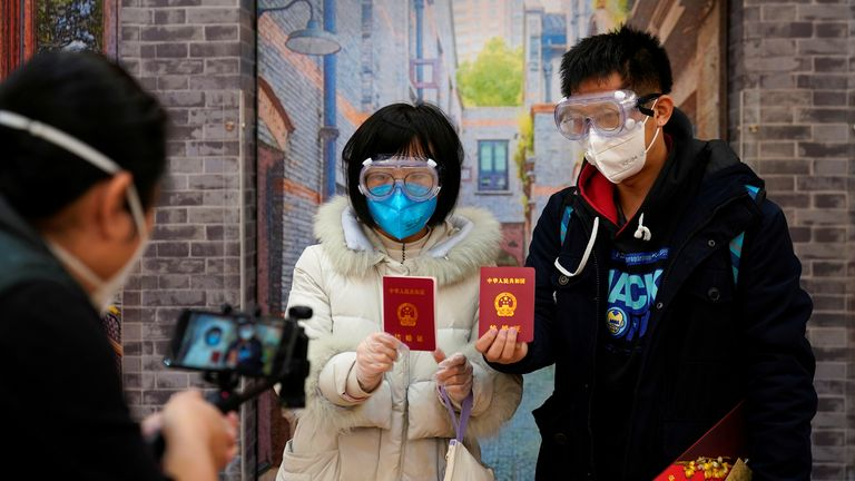 Su, 28 (L) and Jia, 29, got married - wearing face masks - at a registry office on Valentine's Day in Shanghai