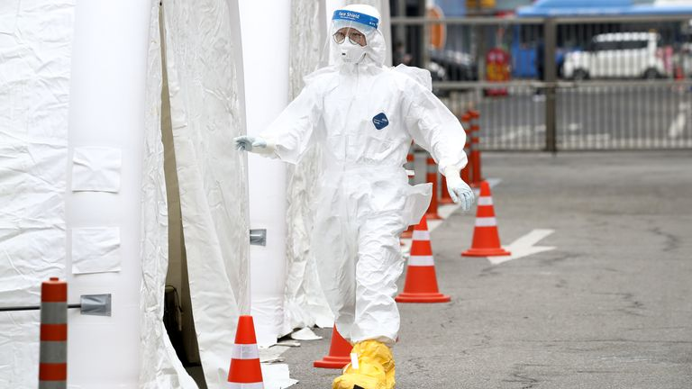 A medic wearing full protective gear walks into a preliminary testing facility in Seoul, South Korea