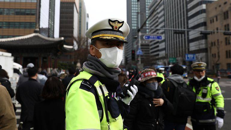 A South Korean policeman wear mask to prevent the coronavirus (COVID-19) walks along the street on February 22, 2020 in Seoul, South Korea. South Korea reported 229 new cases of the coronavirus (COVID-19) bringing the total number of infections in the nation to 433