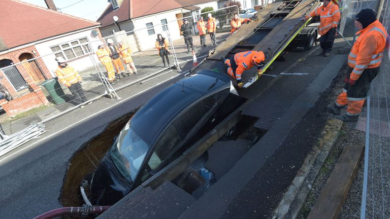 A Toyota car is removed from a sinkhole which appeared overnight in Hatch Road, Brentwood, in the aftermath of Storm Ciara, which hit the country Sunday. PA Photo. Picture date: Monday February 10, 2020. See PA story WEATHER Storm. Photo credit should read: Nick Ansell/PA Wire