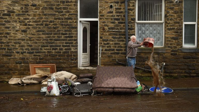 A man empties a bucket of water over debris outside a house in Mytholmroyd, West Yorkshire