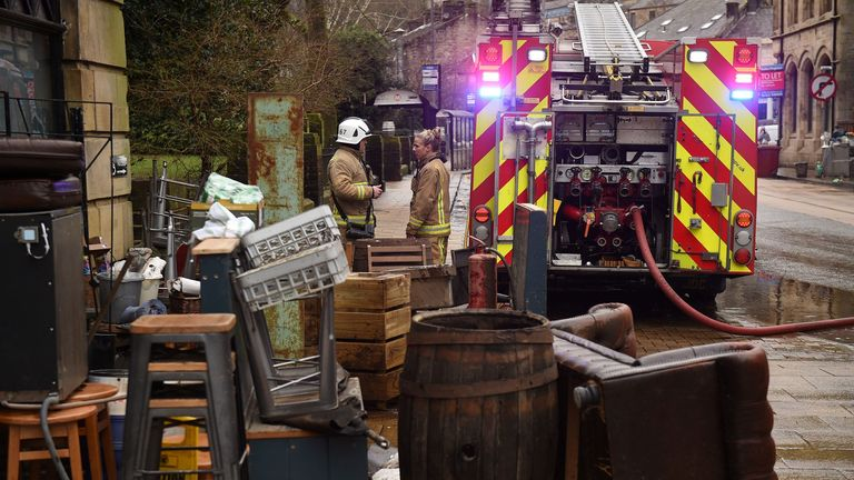 Fire crews help with the clean up efforts outside a business in Hebden Bridge, northern England
