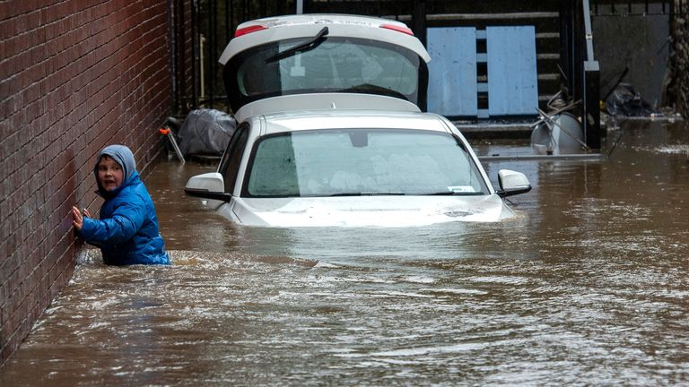A boy wades towards a flooded alleyway in Pontypridd, South Wales. Pic: Neil Munns/EPA-EFE/Shutterstock