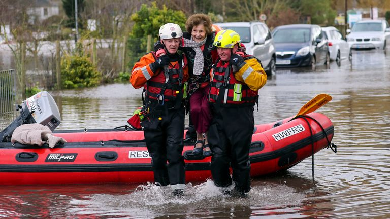 A woman is rescued from floodwaters in Whitchurch, Herefordshire