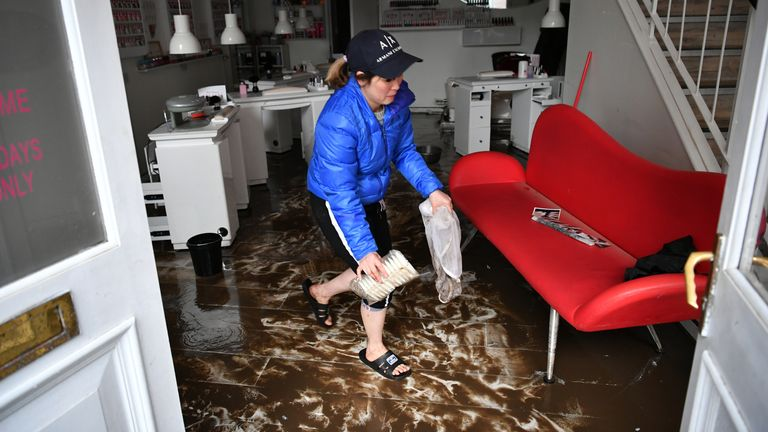 An employee cleans a nail salon hit by floods in Pontypridd