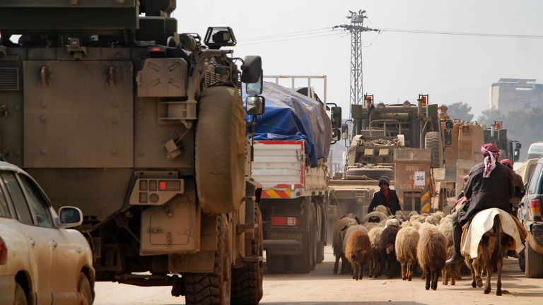 A sheep herder alongside a Turkish military convoy in the town of Bardaqly in Idlib province