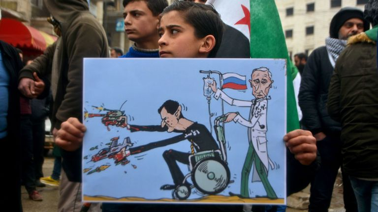 A young Syrian holds a caricature of Syrian President Bashar al Assad and Russian President Vladimir Putin at a protest in the city of Idlib