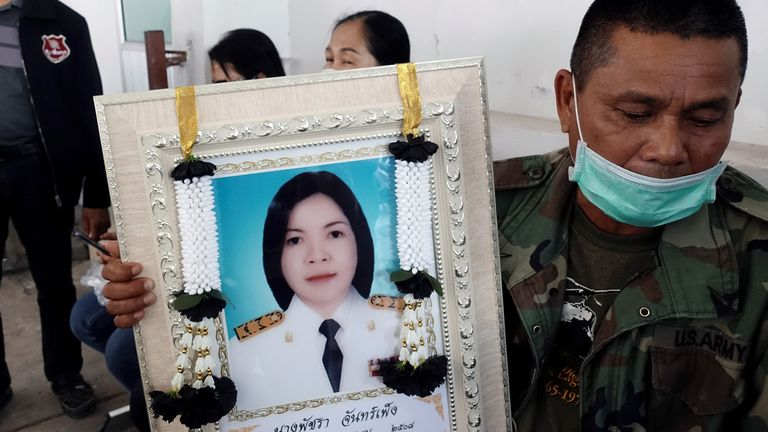 A relative holds a picture of Patchara Chanpeng, one of the gunman's victims