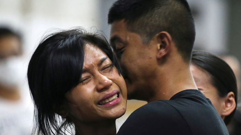 The children of Captain Siriwiwat Sangprasita, a victim of the shopping mall massacre, comfort each other
