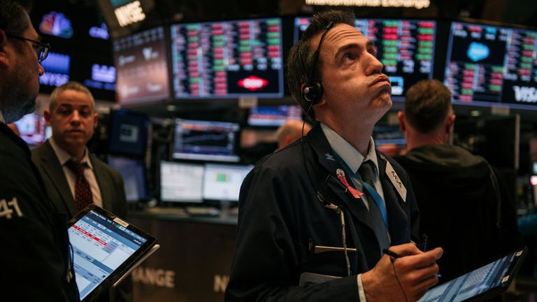 Traders work through the closing minutes of trading Tuesday on the New York Stock Exchange floor on February 25, 2020 in New York City
