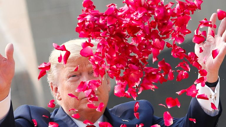 Donald Trump sprays flower petals during a wreath laying ceremony at Mahatma Gandhi's memorial in New Delhi
