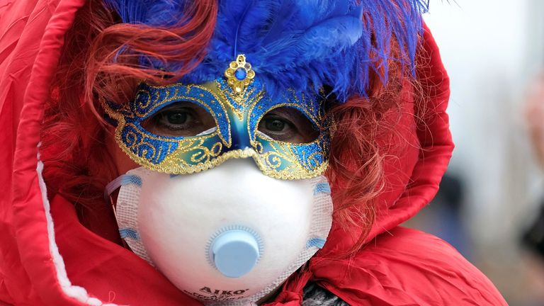 Masked carnival reveller wears protective face mask at Venice Carnival, which the last two days of, as well as Sunday night's festivities, have been cancelled because of an outbreak of coronavirus, in Venice, Italy February 23, 2020