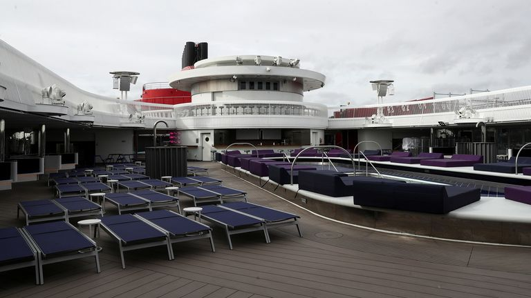 Sun loungers sit on the deck of a Virgin Voyages Scarlet Lady cruise liner