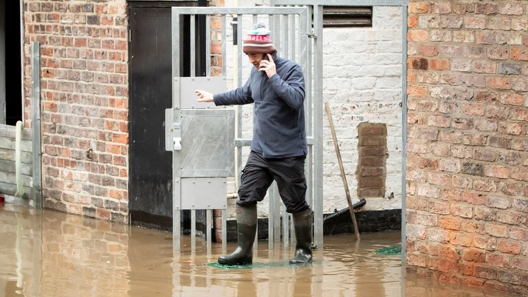 A man navigates flood water in York after the River Ouse burst its banks