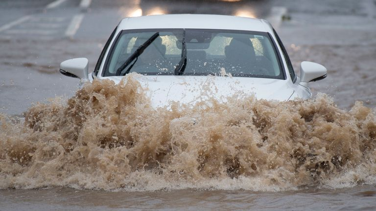 Cars drive through a flooded part of the A48 road at Bonvilston