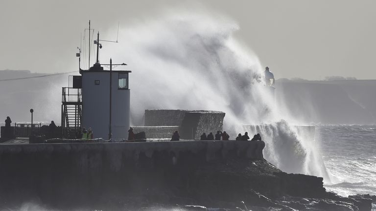 Waves crash over the lighthouse at Porthcawl, South Wales