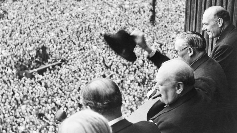 Churchill waves to the crowds in Whitehall on VE Day
