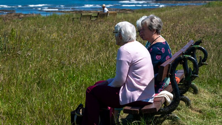 Three women looking out over the North Sea from the vantage point of a park bench looking towards the Farne islands with seahouses harbour in the background.