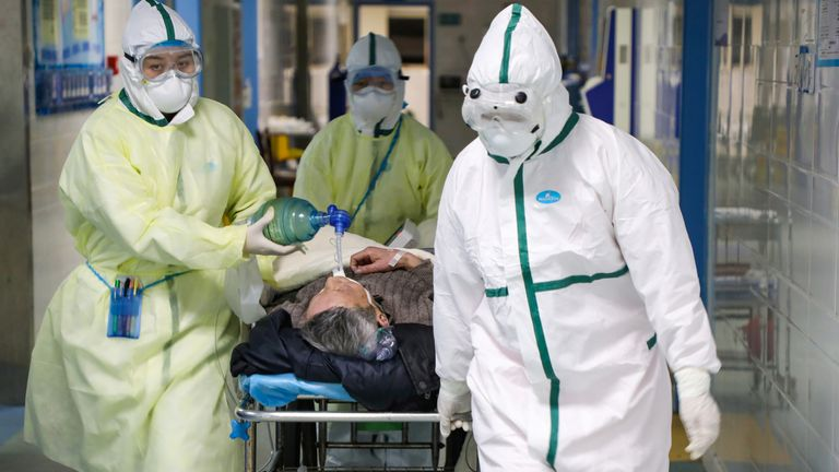 Medical workers in protective suits move a patient in a hospital in Wuhan