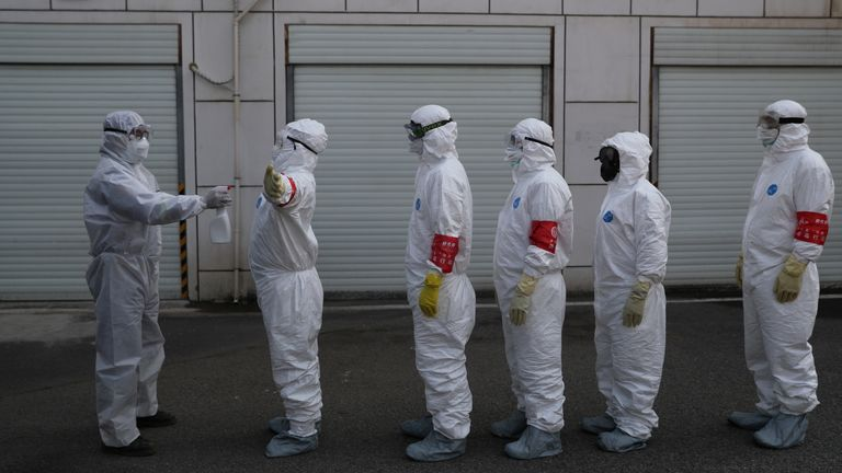 Volunteers in protective suits are disinfected in Wuhan