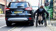 HR55PP Wheelchair user struggles to pass by badly parked car on pavement and double yellow lines in Brighton UK