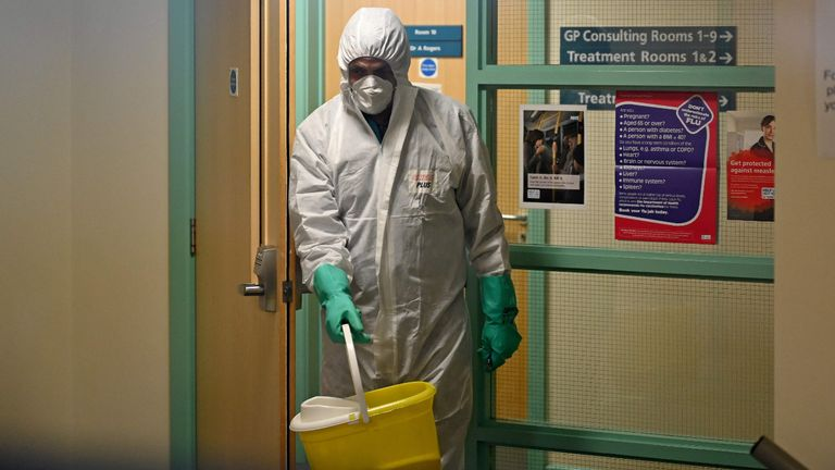 """In this photograph taken through a window, a worker in protective clothing, including face mask and gloves, is pictured carrying a bucket as he works inside of at the Warmdene doctor's Surgery at County Oak Medical Centre in Brighton, southern England on February 10, 2020, after it closed for """"urgent operational health and safety reasons"""", following reports a member of staff was infected with the 2019-nCoV strain of the novel coronavirus, Covid-19.. - The British government on Monday warned the outbreak of novel coronavirus was a """"serious and imminent threat"""" and reported four new cases that brought the total recorded in the country to eight. Two hospitals The Royal Free and Guys and St Thomas', have both been designated as """"isolation"""" facilities, with both currently housing Britons who have returned from Wuhan, the Chinese city at the centre of the outbreak. (Photo by Glyn KIRK / AFP) (Photo by GLYN KIRK/AFP via Getty Images)"""