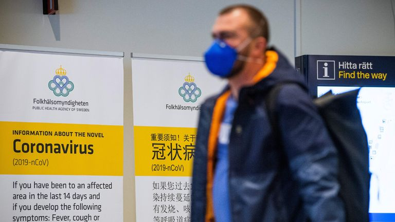 (FILES) In this file photo taken on March 5, 2020 a passenger arriving in Stockholm's Arlanda airport is greeted by signs produced by the public health agency advising travelers what to do if they show symptoms of infection by the new coronavirus after arriving in Sweden. - No one in northern Europe has yet succumbed to the disease, which has been described as more deadly than the seasonal flu, which claims hundreds of victims in the region every year. (Photo by Jonathan NACKSTRAND / AFP) (Photo by JONATHAN NACKSTRAND/AFP via Getty Images)