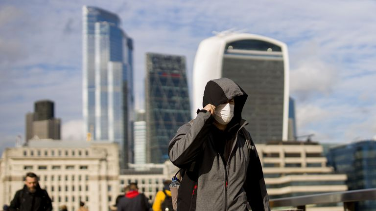 A man wearing a protective face mask, walks across London Bridge as Britain braces itself for an increase in cases of the Coronavirus, on March 11, 2020 in central London. - The Bank of England slashed its interest rate to a record low 0.25 percent on Wednesday as part of coordinated emergency action with the UK government to combat the economic fallout from the coronavirus outbreak. (Photo by Tolga Akmen / AFP) (Photo by TOLGA AKMEN/AFP via Getty Images)