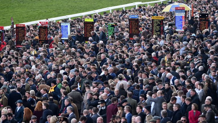 Racegoers attend the final day of the Cheltenham Festival horse racing meeting at Cheltenham Racecourse in Gloucestershire, south-west England, on March 13, 2020. (Photo by Glyn KIRK / AFP) (Photo by GLYN KIRK/AFP via Getty Images)